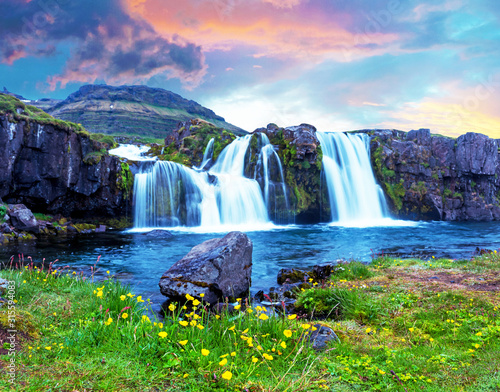 Beautiful terrific landscape with yellow flowers and big stone near waterfall Kirkjufell in Iceland at sunset. Exotic countries. Amazing places. Popular tourist atraction.  - 315594083
