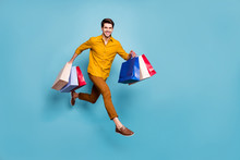 Full Length Profile Photo Of Funny Guy Jumping High Running Fast Carry Many Bags Rushing Next Shop Store Wear Yellow Shirt Pants Isolated Blue Color Background