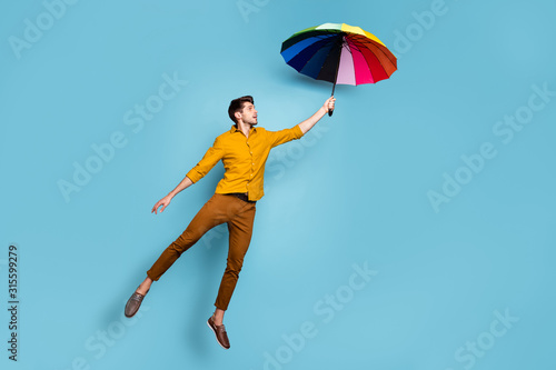 Full length photo of crazy guy jumping high holding colored bright umbrella flyi Fototapeta