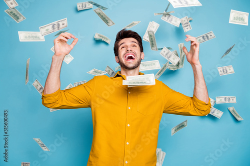 Fototapeta Photo of screaming excited emotional guy having won jackpot in lottery smiling toothily isolated over blue pastel color background in yellow shirt obraz