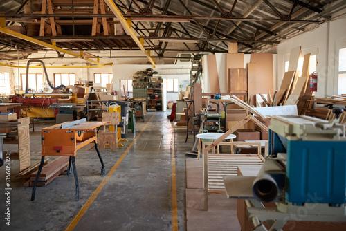 Obraz Wood and machinery in a large carpentry workshop - fototapety do salonu
