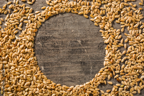 Obraz Golden flax seeds on wooden table. Copy space - fototapety do salonu