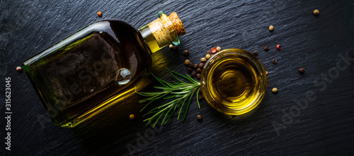 Fototapeta Extra virgin olive oil in a glass bottle, rosemary and peppercorns obraz