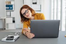 Amused Businesswoman Peering Around Her Laptop
