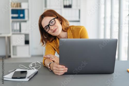 Photo Amused businesswoman peering around her laptop