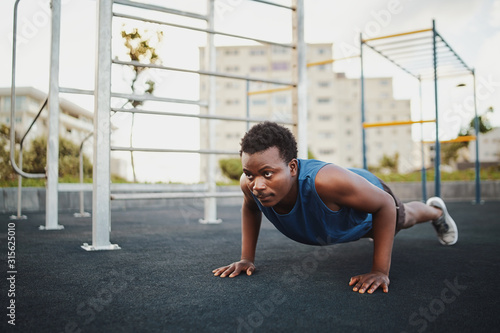 Tela Fit young african american man working out on crossfit strength training doing p