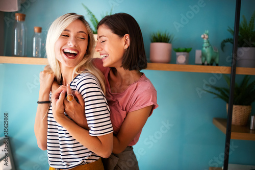 Cheerful lesbians embrace passioantely and have fun together Wallpaper Mural