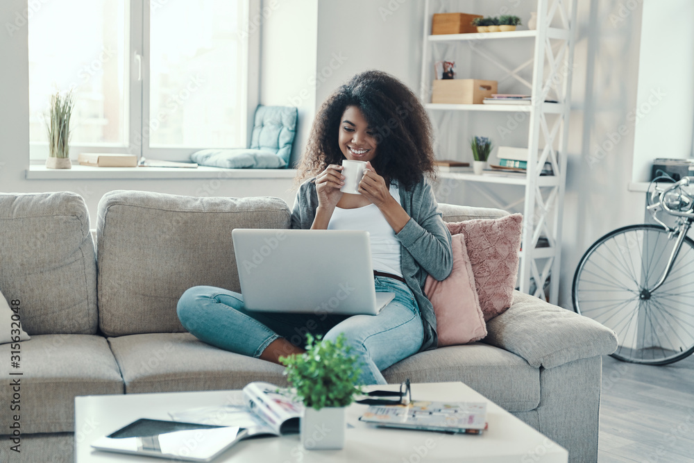 Fototapeta Attractive young African woman in casual clothing drinking hot tea and using laptop while resting at home