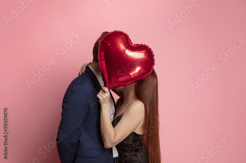 Happy holding balloons shaped hearts. Valentine's day celebration, happy caucasian couple on coral background. Concept of human emotions, facial expression, love, relations, romantic holidays. - 315634870