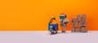 canvas print picture - Robot storekeeper uploads parcels into an autonomous delivery robotic courier. Automation service of warehousing and shipment. Orange background, copy space