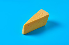 One Piece Of Cheese In Form Of Triangle Lies On Blue Desk On Kitchen Or Market. Close-up