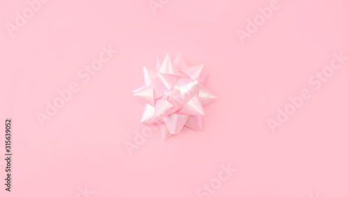 Fototapety, obrazy: Festive pink background. Bow on light pink pastel background. Christmas, Wedding. Birthday, Happy woman's day. Mothers Day. Valentine's Day. Flat lay, top view. Copy space