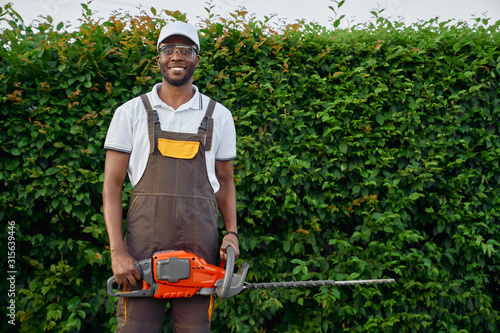 Fotografie, Tablou Front view of afro gardener with gasoline hedge trimmer