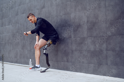 Full length of handsome caucasian sportsman with artificial leg leaning on wall, looking at wristwatch and resting from running Wallpaper Mural