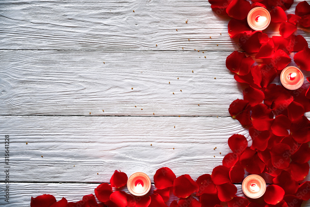 Fototapeta Red rose petals and red burning candles on a white wooden background. St. Valentine's Day background.
