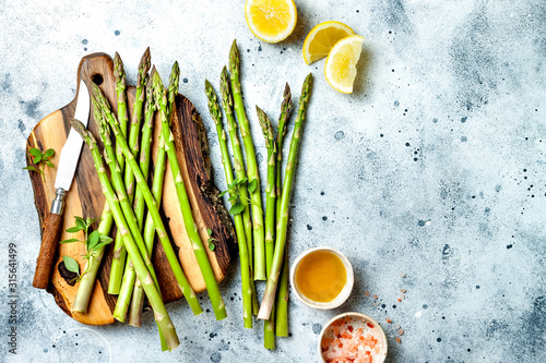 Bunch of fresh green asparagus on wooden board with olive oil, lemon and seasonings Canvas Print