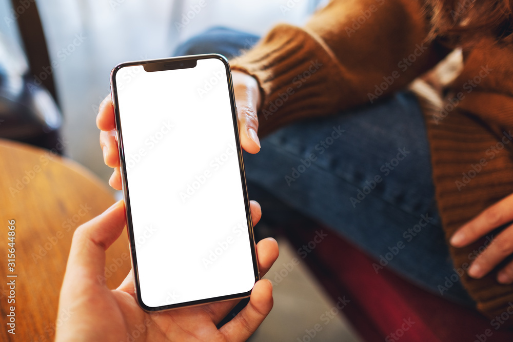 Fototapeta Mockup image of a woman holding and showing white mobile phone with blank black desktop screen to someone