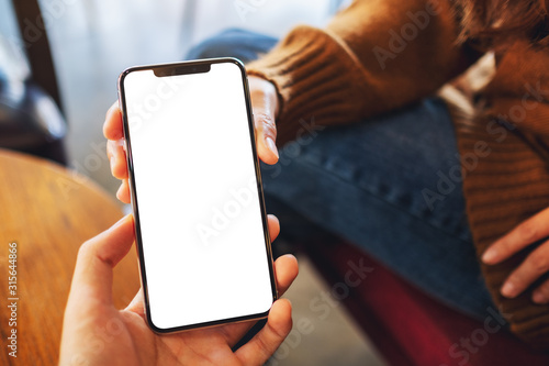 Mockup image of a woman holding and showing white mobile phone with blank black desktop screen to someone - 315644866