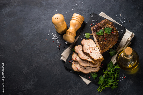 Fototapeta  Baked pork meat ham on black kitchen table.