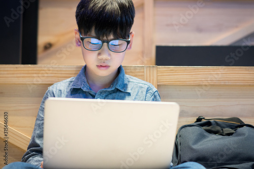 Photo Smart asian preteen boy with blue light blocking glasses is online learning with his laptop
