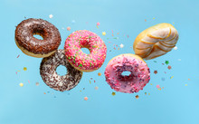 Flying Donuts. Mix Of Multicolored Doughnuts With Sprinkel On Blue Background.