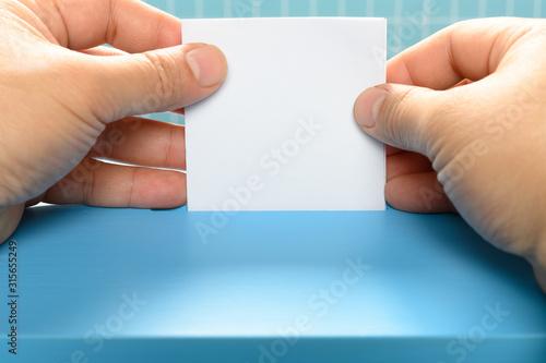 Fényképezés  man inserting his ticket to a vote box