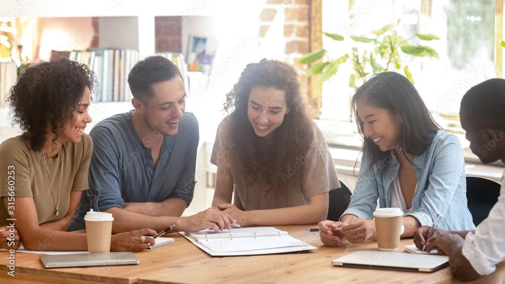 Fototapeta Smiling multiracial people discuss paperwork at meeting