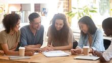 Smiling Multiracial People Discuss Paperwork At Meeting