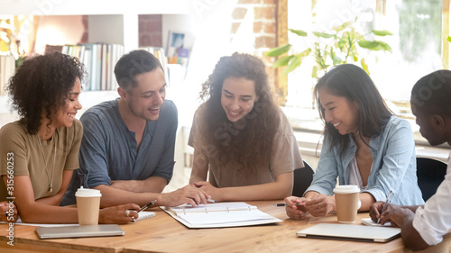 Obraz Smiling multiracial people discuss paperwork at meeting - fototapety do salonu