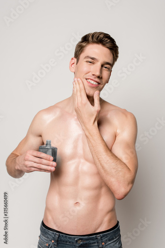 Photo smiling sexy man with muscular torso applying aftershave on face isolated on gre