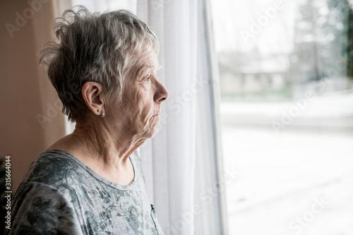 Fototapeta Sad senior woman at home close to window