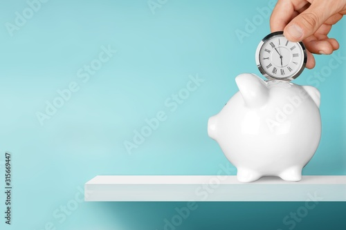 Fotomural Hand depositing  clock  in piggy bank on background
