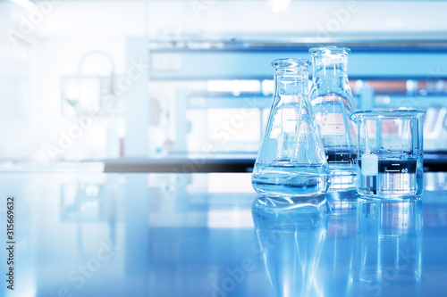 Fototapeta water in beaker and flask glass in chemistry blue science laboratory background obraz