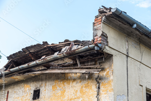Fototapeta Remains of hurricane or earthquake aftermath disaster damage on ruined old houses with collapsed roof and wall with dust in the air obraz