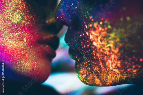 Fotomural Couple kissing in the disco club with fluorescent paintings on the faces