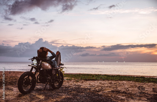 Fotomural Beautiful girl having fun driving her custom cafe racer motorcycle, enjoying the