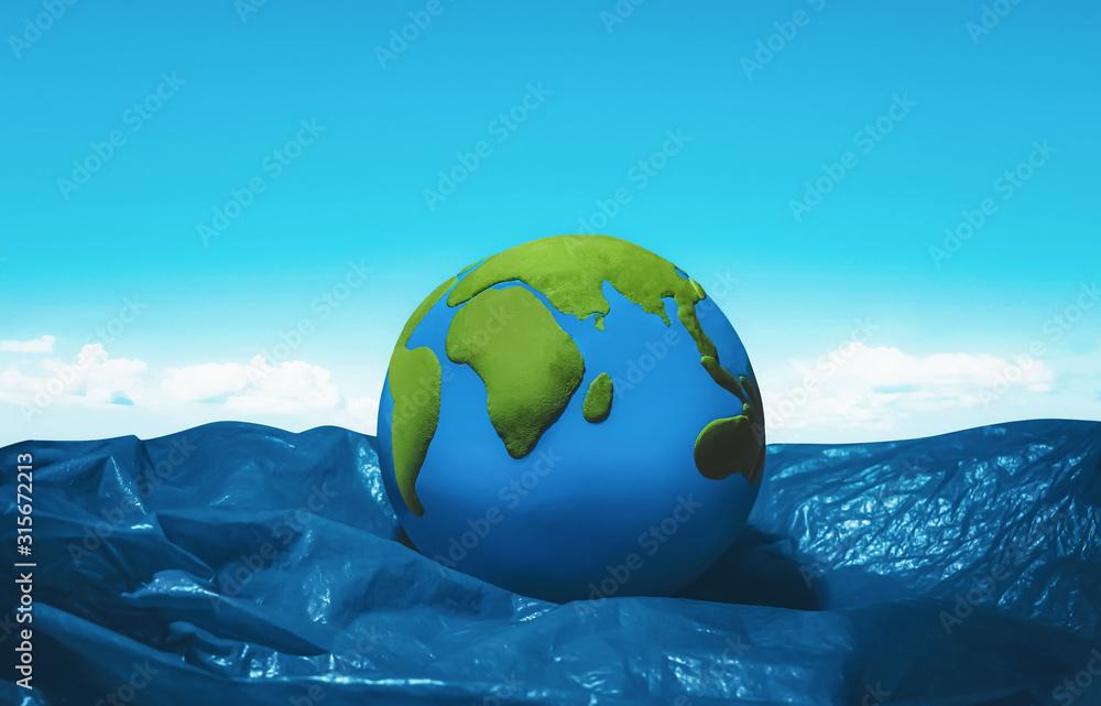 Fototapeta earth floating on blue plastic ocean