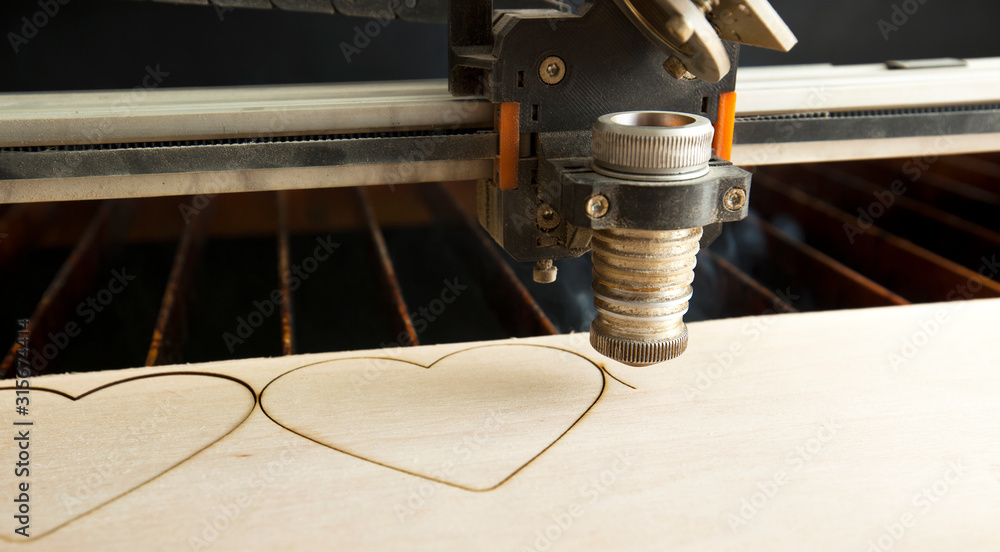 Fototapeta Laser cutting machine is cutting the wooden plank