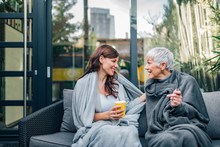Two Women Of Different Age Sitting On The Patio Covered In Blankets And Talking, Portrait.