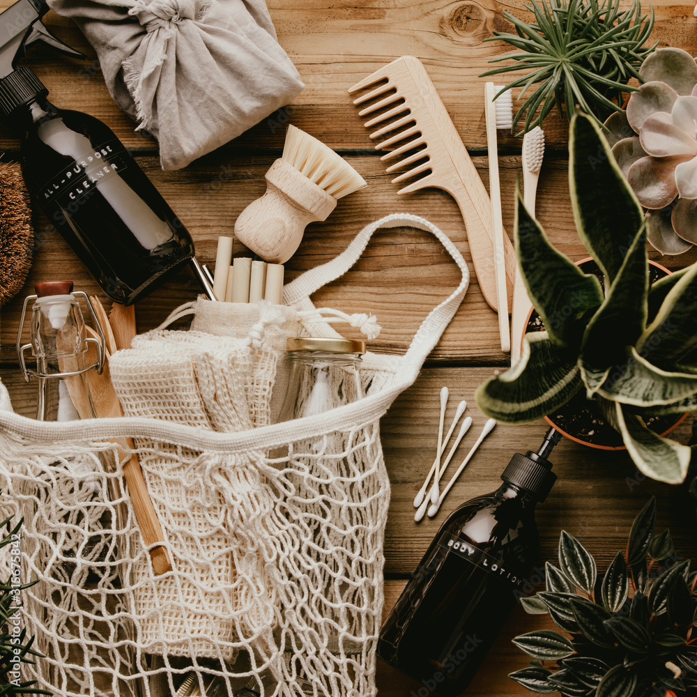 Fototapeta Collection of various succulent plants and Mesh market bag with bamboo cutlery, reusable bottles and eco cotton bags on wooden background