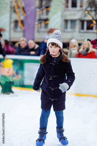 Happy little kid girl in colorful warm clothes skating on a rink of Christmas market or fair. Healthy child having fun on ice skate. Lot of people celebrating holiday and having active winter leisure