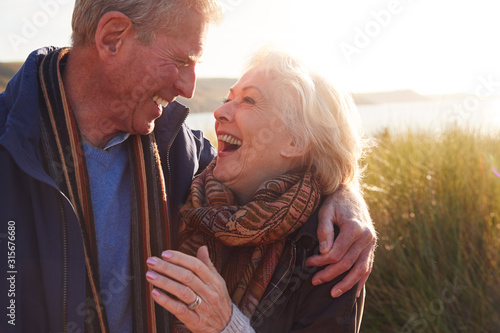 Fotografía Loving Active Senior Couple Hugging As They Walk Through Sand Dunes