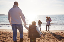 Rear View Of Family Walking Towards Sea Silhouetted Against Sun