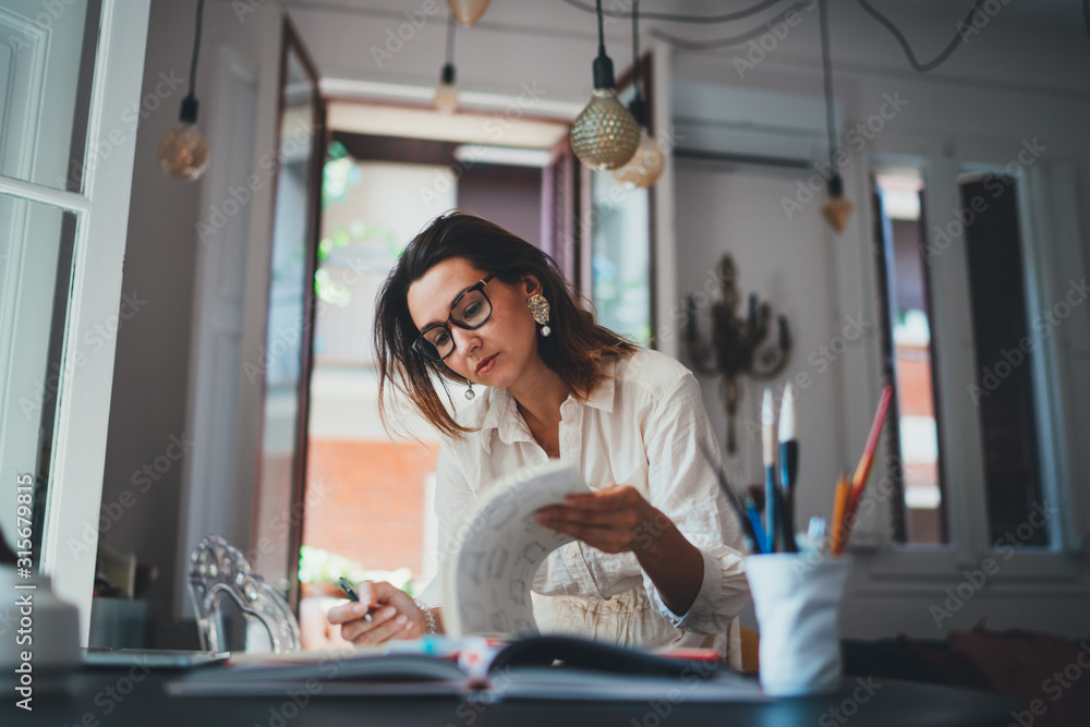 Fototapeta Young creative woman working in designer agency, female small business owner working on social media strategy while sitting in modern loft studio, Successful Owner Project Creative People
