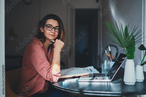 Cuadros en Lienzo Pretty young woman an advertising copywriter in eyeglasses working at home using