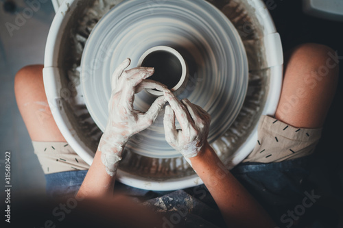 Obrazy nowoczesne   top-view-of-female-potter-s-hands-working-on-pottery-wheels-with-eco-friendly-clay-makes-mug-concept-for-workshop-and-master-class-handcraft-ceramic-art-people