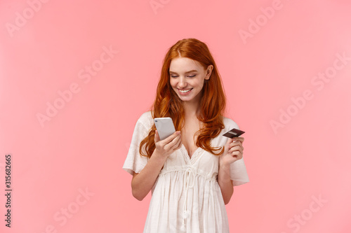 Shopping, easy payment and people concept. Lovely redhead girl in white dress picking present in online store, holding smartphone and credit card, paying via internet for delivery, pink background