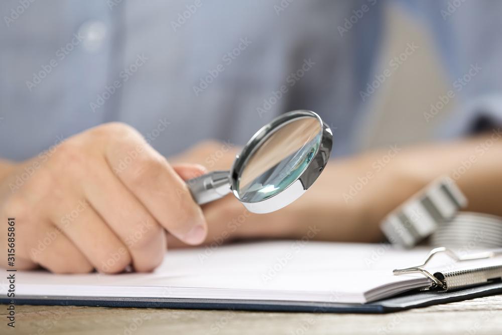 Fototapeta Woman using magnifying glass at table, closeup