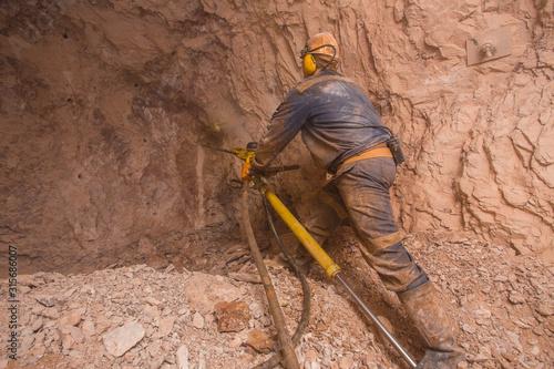 Underground bauxite mine shaft with drilling miner Wallpaper Mural