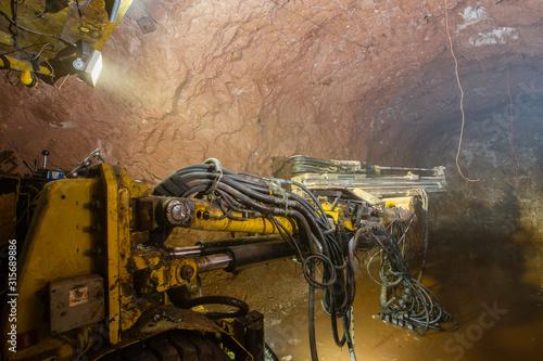 Photo Underground gold bauxite mine shaft tunnel with drilling machine